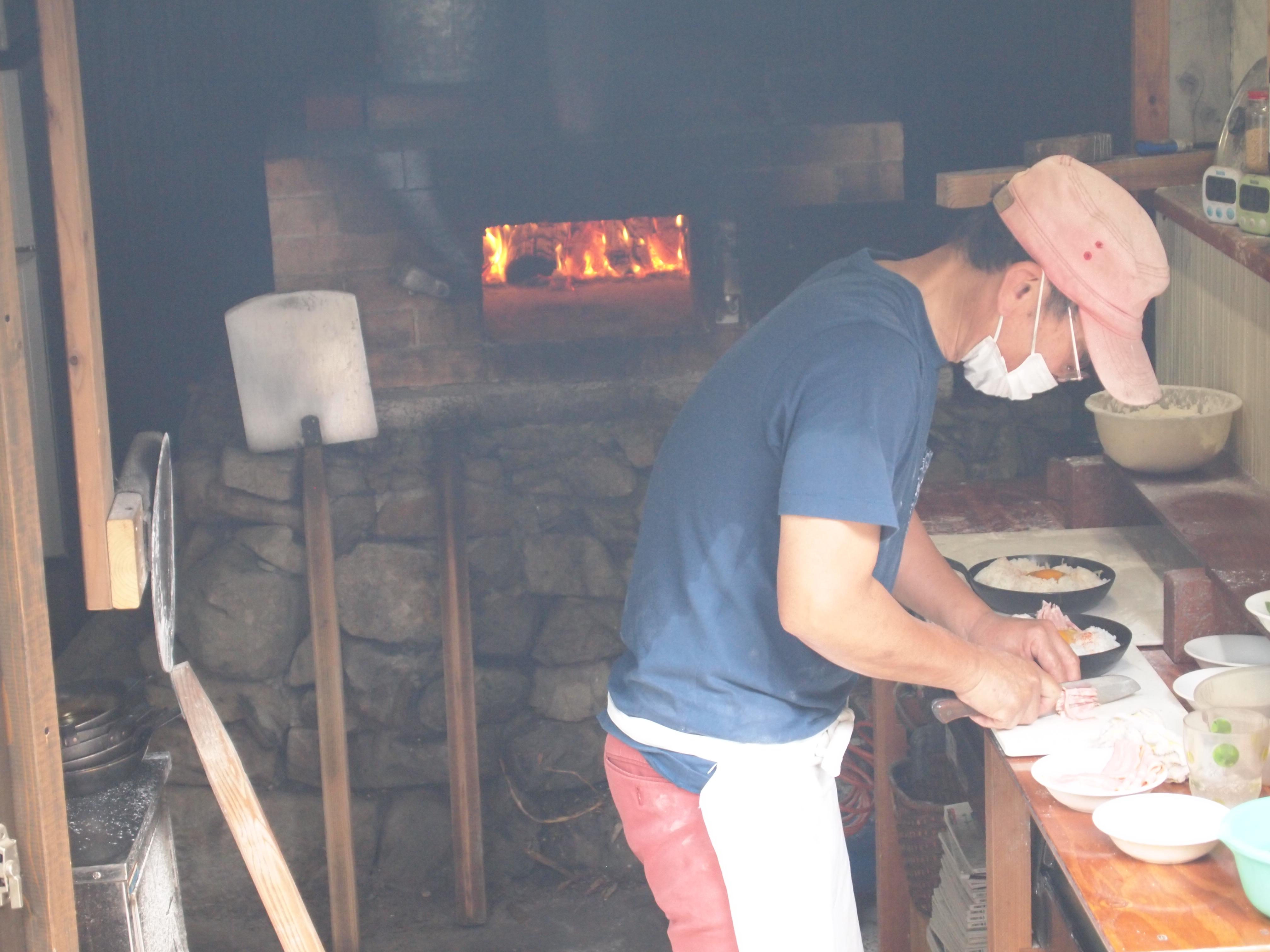 テラス席からは石釜でピザを焼いている姿が見えます。 焼いているのは民宿のご主人。