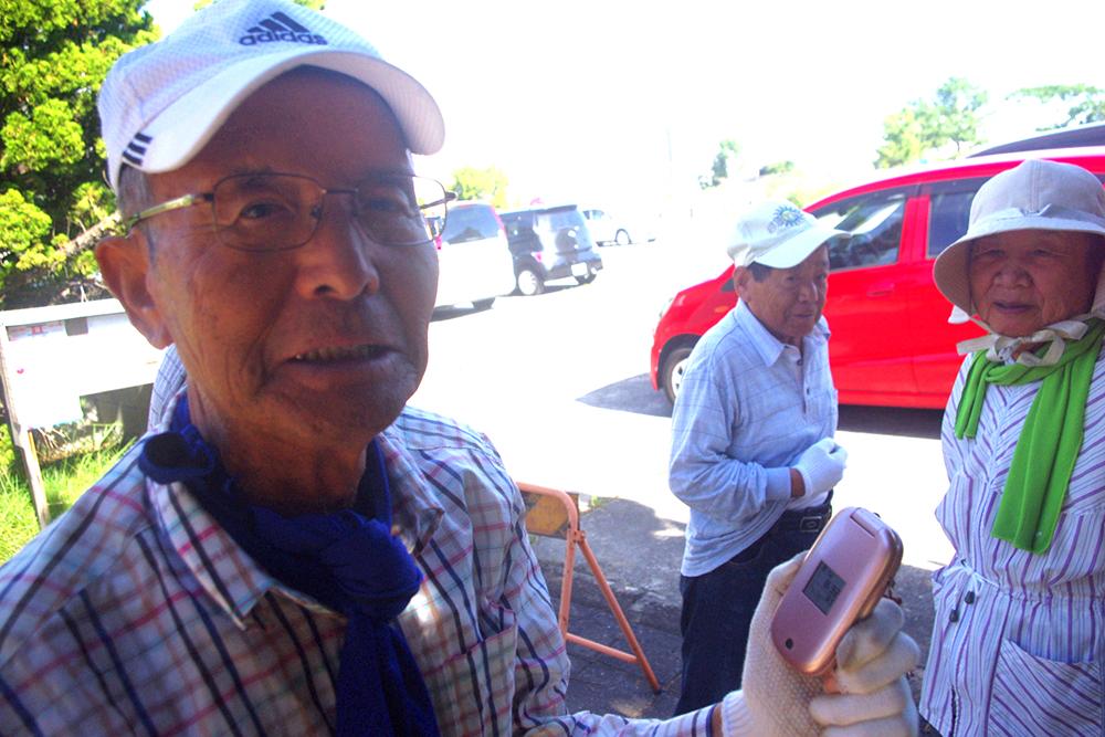 青山さん。御年80歳。キュートなピンクのガラケー。