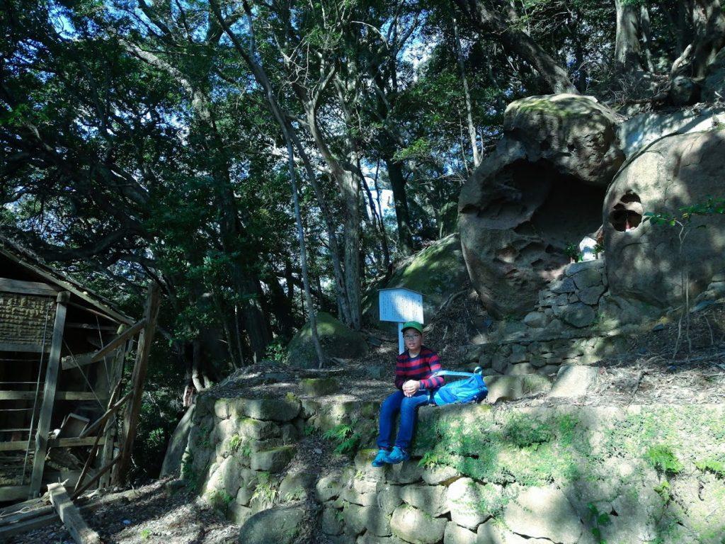 少年の右上にある岩のくぼみに泊観音がある。